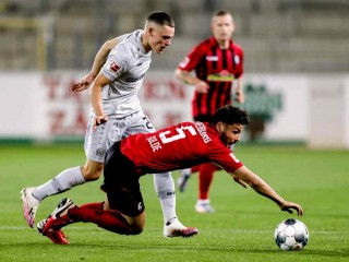 Freiburg's Manuel Gulde in action against Bayer Leverkusen's Florian Wirtz as play resumes behind closed doors following the outbreak of COVID-19. (Reuters Photo)