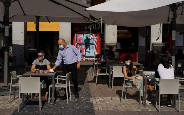 A waiter wearing a protective face mask serves a beverage for a client at an outdoor seating section of a restaurant that reopened for the first time in more than 2 months amid the coronavirus disease (COVID-19) outbreak, at Plaza Mayor Square in Madrid, Spain on May 25, 2020. (REUTERS Photo)