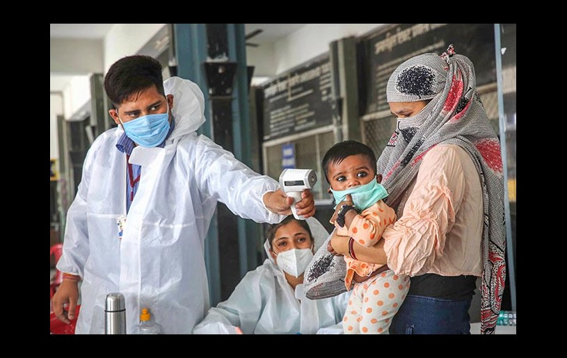 Migrants being screened by medics as they arrive to board a special train for Udhampur in Jammu and Kashmir, during covid-19 lockdown, at Habibganj Railway Station in Bhopal, Monday, May 18, 2020. (PTI Photo)