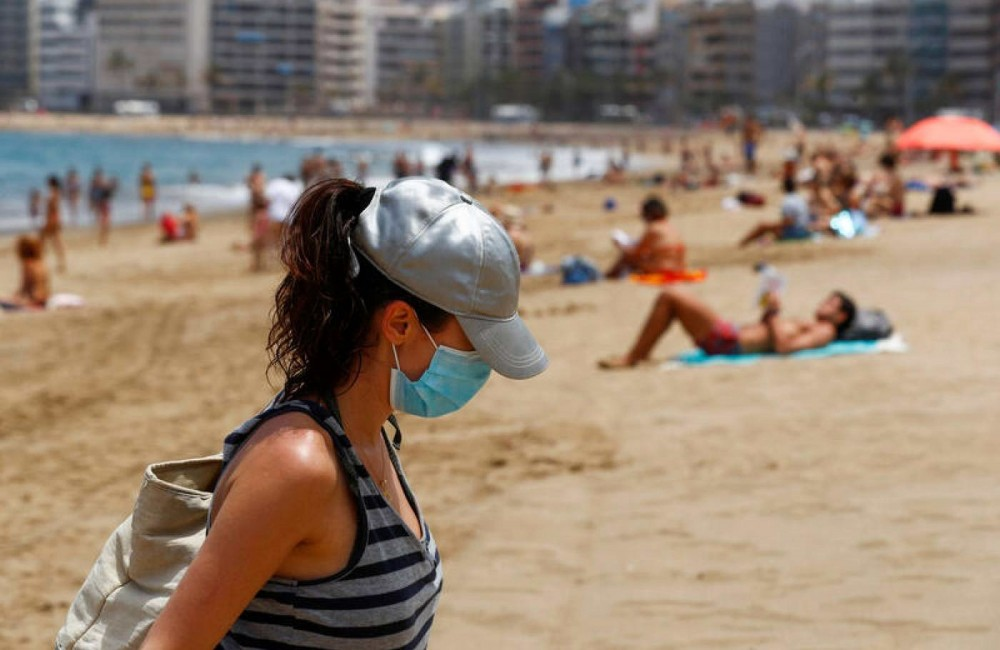 A woman with a face mask leaves the Las Canteras beach amid the coronavirus disease (COVID-19) outbreak, on the island of Gran Canaria, Spain May 25, 2020. (Reuters Photo)