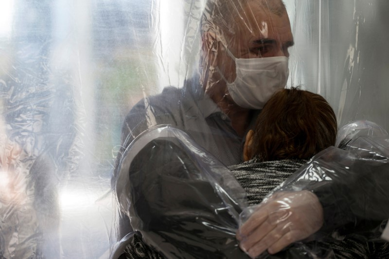 Ossimar Silva hugs his mother Carmelita Valverde, 85, through a plastic curtain at the 3i Bem-Estar - Residencial Senior nursing home, amid the coronavirus disease (COVID-19) outbreak, in Sao Paulo, Brazil May 30, 2020. Picture taken May 30, 2020.  (Reuters Photo)