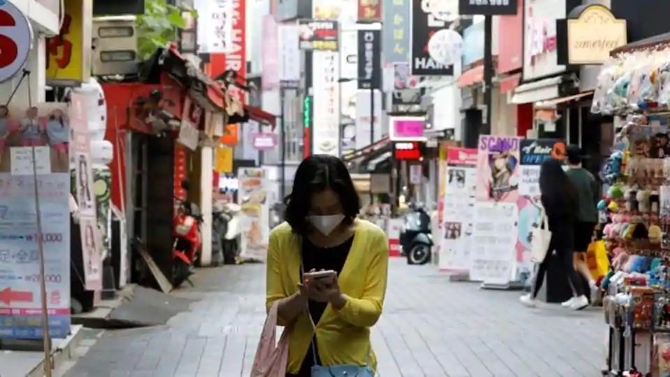 A woman wearing a mask looks at her mobile phone amid social distancing measures to avoid the spread of the novel coronavirus, in Myeongdong shopping district in Seoul, South Korea on May 28, 2020. (Reuters File Photo )