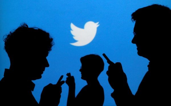 People holding mobile phones are silhouetted against a backdrop projected with the Twitter logo in this illustration picture taken in Warsaw September 27, 2013. (REUTERS File Photo)