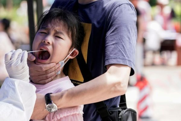 A child reacts while undergoing nucleic acid testing in Wuhan, the Chinese city hit hardest by the coronavirus disease (COVID-19) outbreak, Hubei province, China on May 16, 2020. (REUTERS File Photo)