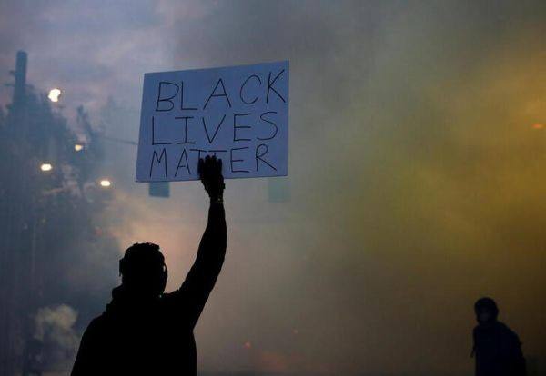 "A person holds a ""Black Lives Matter"" sign as a heavy cloud of tear gas and smoke rises after being deployed by Seattle police as protesters rally against police brutality and the death in Minneapolis police custody of George Floyd, in Seattle, Washington, US on June 1, 2020.  (REUTERS Photo)"