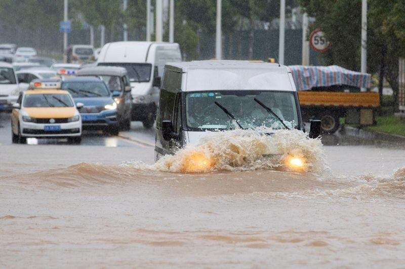 A vehicle travels through a flooded section of a road following heavy rainfall in Wuhan, Hubei province, China on July 6, 2020. (REUTERS Photo)