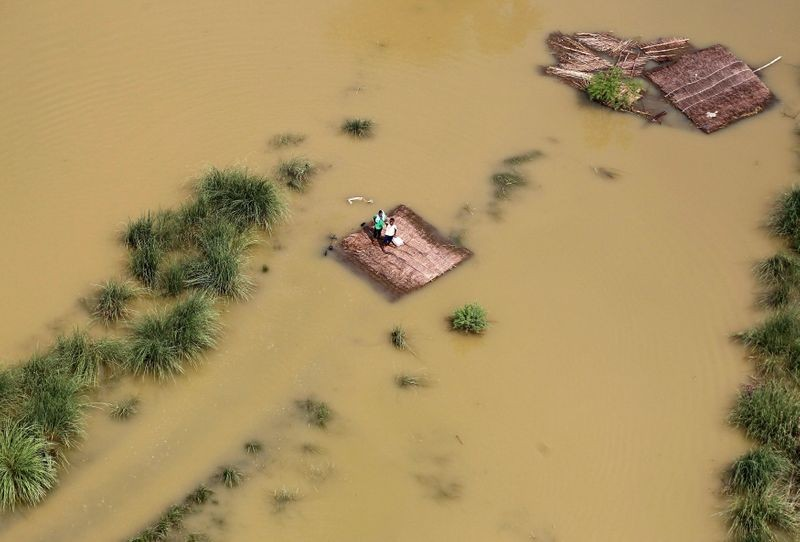 People affected by flooding stand on a partially submerged house as they wait to receive food parcels in the outskirts of Allahabad, India, August 25, 2016. REUTERS/Jitendra Prakash/File photo