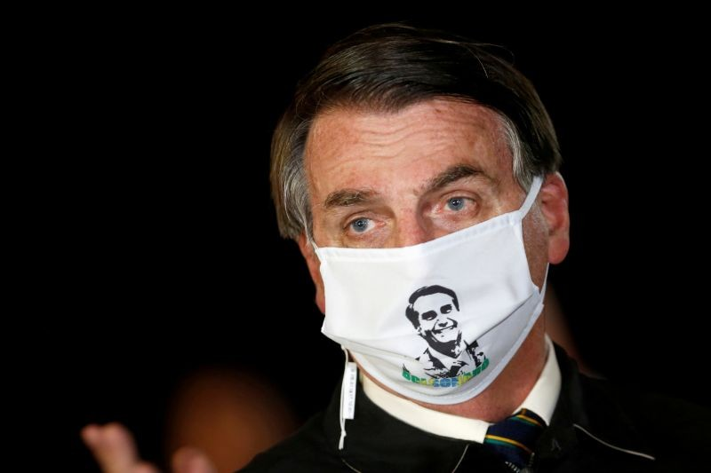 Brazil's President Jair Bolsonaro speaks with journalists while wearing a protective face mask as he arrives at Alvorada Palace, amid the coronavirus disease (COVID-19) outbreak, in Brasilia, Brazil on May 22, 2020. (REUTERS File Photo)