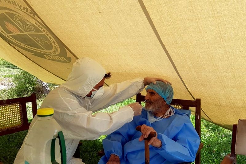 A paramedic wearing protective gear takes a nasal swab of 103 year-old Abdul Alim, to be tested for the coronavirus disease (COVID-19), at the Aga Khan Health Services Emergency Response Centre in Booni, Chitral, Pakistan in this undated photograph provided to Reuters. (REUTERS Photo)