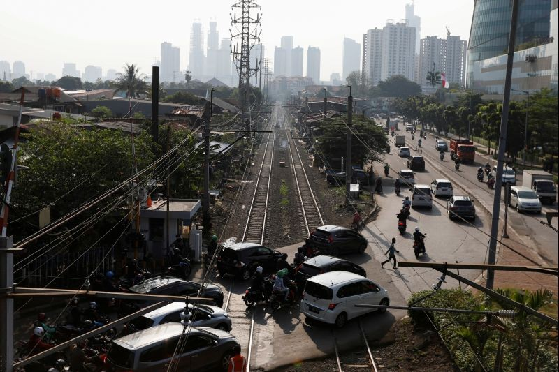 A man crosses a road during morning rush hours after the government eased restrictions following the coronavirus disease (COVID-19) outbreak, near a densely populated residential area in Jakarta, Indonesia on July 8, 2020. (REUTERS Photo)