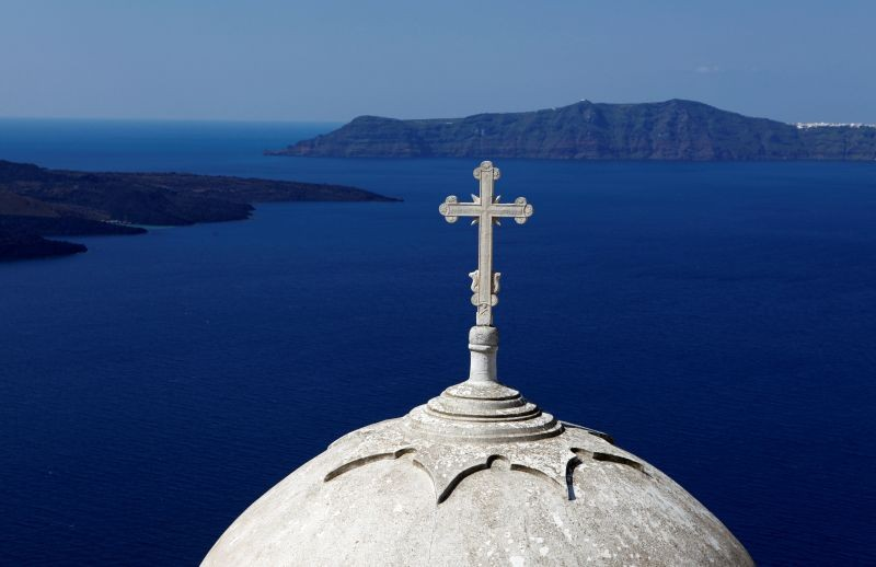 Volcanic islets are seen behind a Greek Orthodox church built on the edge of the caldera at the volcanic island of Santorini. (REUTERS File Photo)
