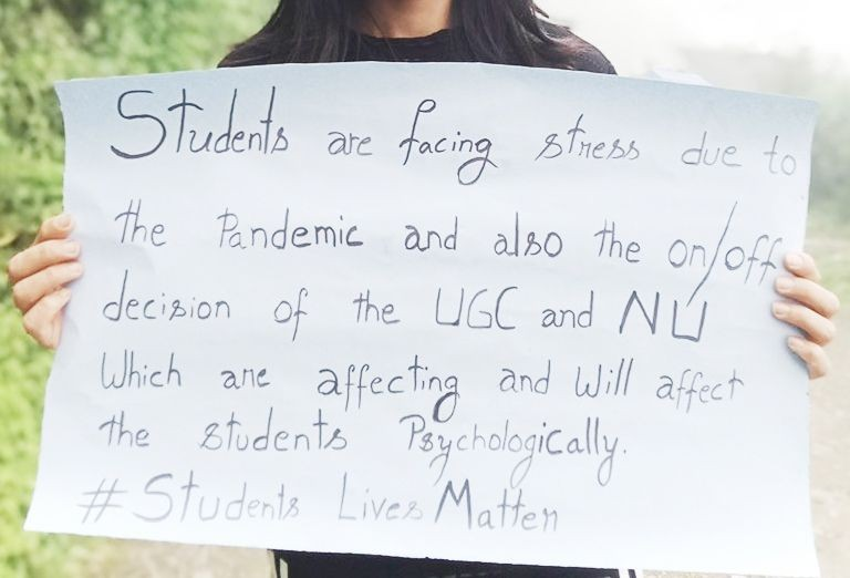 A students holds up a placard as part of an online campaign opposing the UGC's move to hold examinations during the pandemic.