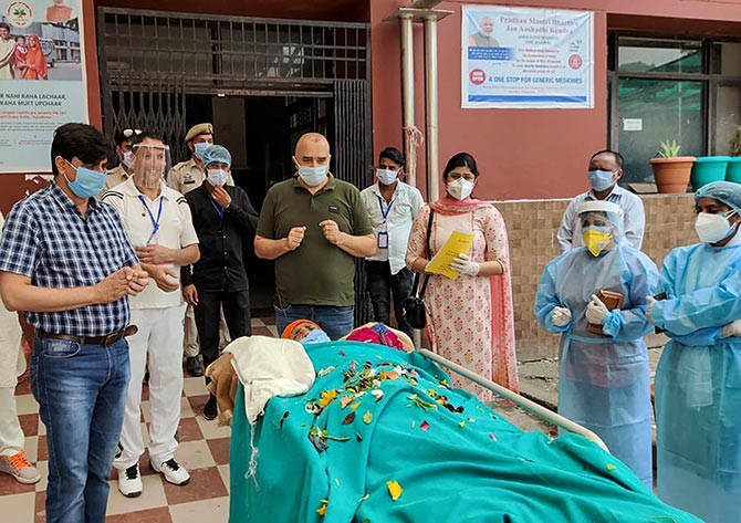 Medics applaud a 98-yr old woman as she is discharged from the Government Medical College Hospital after recovering from COVID-19, in Rjouri, J-K, on Saturday. Photograph: PTI Photo