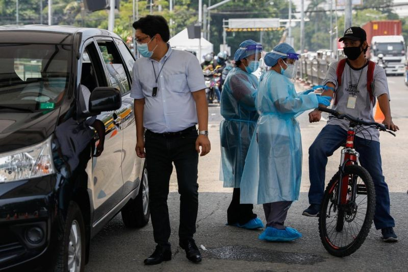 Healthcare workers take blood samples from a bike rider at a coronavirus disease (COVID-19) drive-thru testing center in Manila, Philippines on July 15, 2020. (REUTERS File Photo)