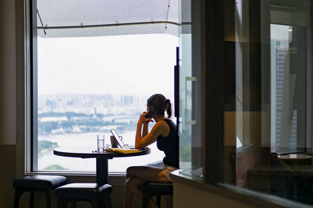 A woman answers a call while looking out the window in co-working space The Great Room's Centennial Tower location in Singapore, July 2, 2019. REUTERS/Loriene Perera