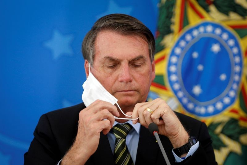 Brazil's President Jair Bolsonaro adjusts his protective face mask during a press statement to announce federal judiciary measures to curb the spread of the coronavirus disease (COVID-19) in Brasilia, Brazil on March 18, 2020. (REUTERS File Photo)