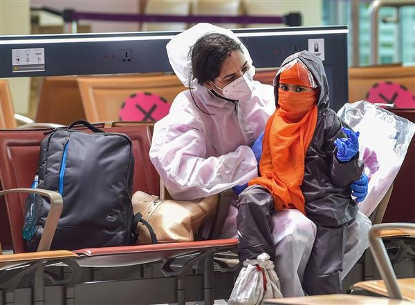 A passenger and her child wearing protective suits wait to board a plane at Kempegowda International airport, in Bengaluru,. PTI Photo