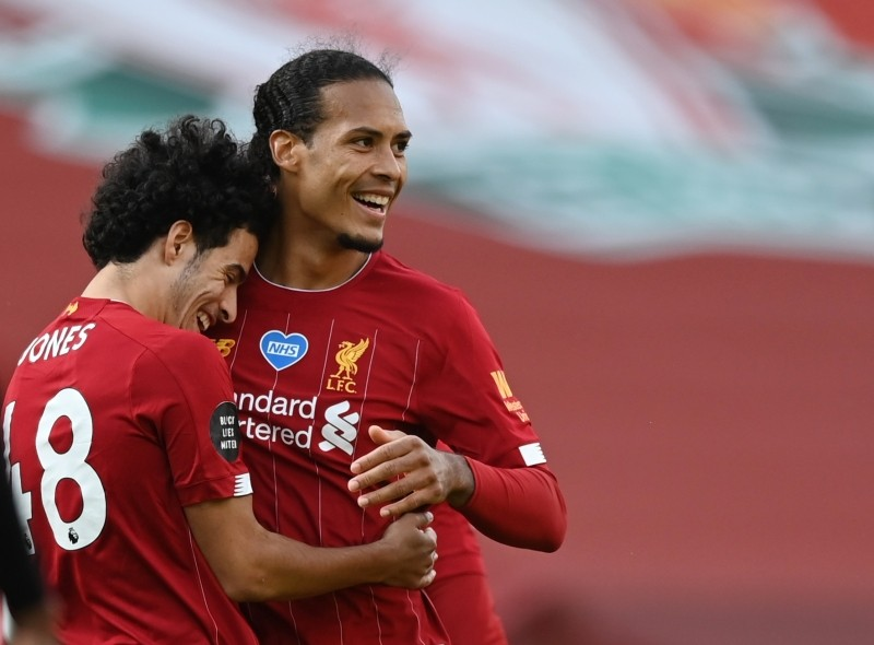 Liverpool's Curtis Jones celebrates with Virgil van Dijk after the match, as play resumes behind closed doors following the outbreak of the coronavirus disease (COVID-19) Shaun Botterill / Pool via REUTERS