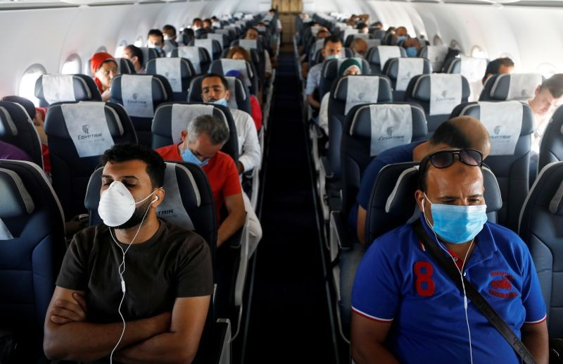Passengers wearing protective face masks sit on a plane at Sharm el-Sheikh International Airport, following the outbreak of the coronavirus disease (COVID-19), in Sharm el-Sheikh, Egypt on June 20, 2020. (REUTERS File Photo)