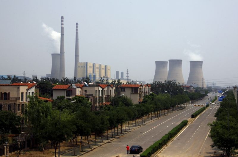 The cooling towers and chimneys from a coal-burning power station can be seen behind a man standing next to his car in a newly constructed residential area in Beijing  on June 1, 2012. (REUTERS File Photo)