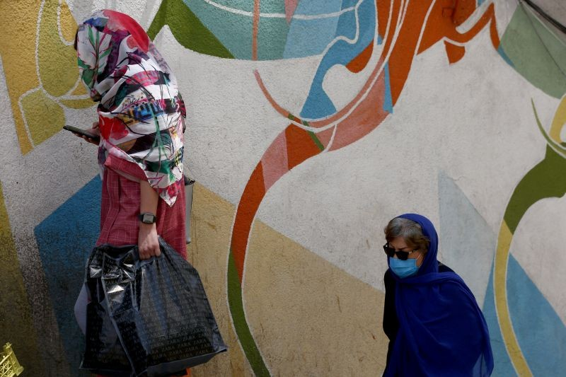 A woman wearing a protective face mask walks past a painted wall in a bazar following the outbreak of the coronavirus disease (COVID-19), north of Tehran, Iran on July 8, 2020. (REUTERS Photo)