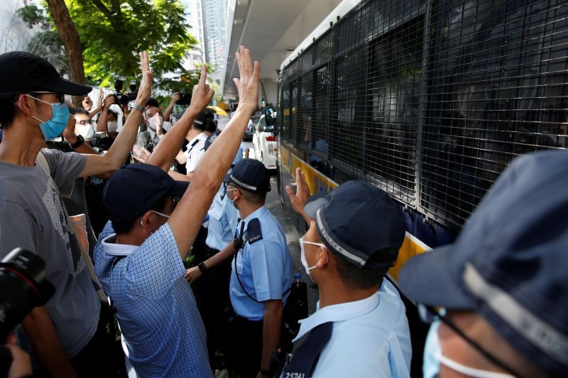 Supporters of Tong Ying-kit, the first person charged under the new national security law, greet a prison van outside West Kowloon Magistrates' Courts in Hong Kong, China on July 6. (REUTERS Photo)