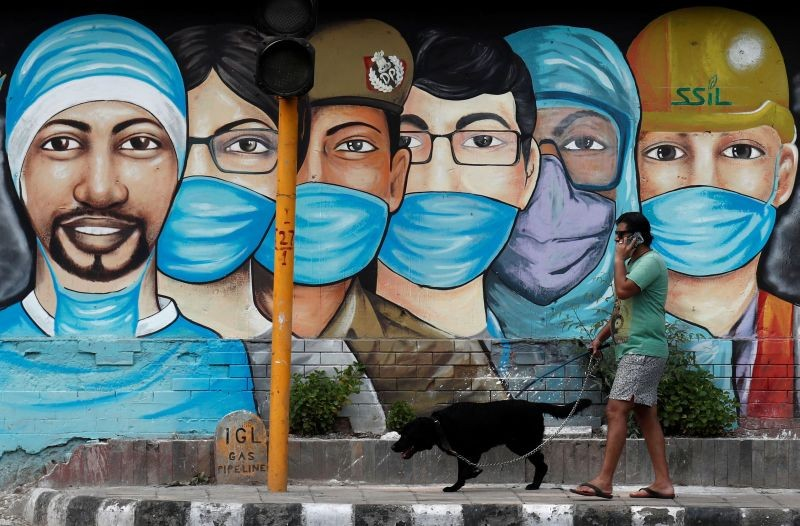 A man walks his dog past a graffiti on a road, amidst the spread of the coronavirus disease (COVID-19), in New Delhi on July 17, 2020. (REUTERS Photo)