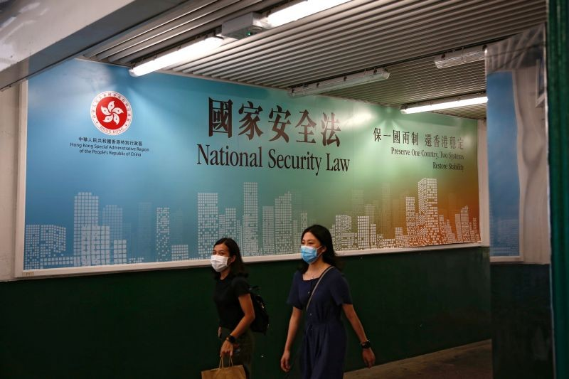 Women walk past a government-sponsored advertisement promoting the new national security law as a meeting on national security legislation takes place in in Hong Kong, China on June 29, 2020. (REUTERS File Photo)