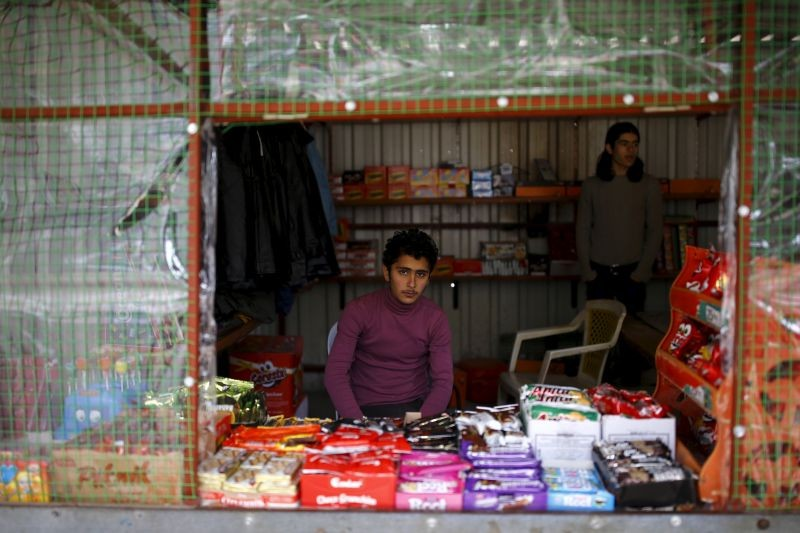 Syrian refugee Resad Bekur, 18, poses in a shop where he works in Yayladagi refugee camp in Hatay province, near the Turkish-Syrian border, Turkey on December 16, 2015. Syria's conflict has left hundreds of thousands dead, pushed millions more into exile, and had a profound effect on children who lost their homes or got caught up in the bloodletting. The drawings of young refugees living in Turkey show their memories of home and hopes for its future. The pictures also point to the mental scars borne by 2.3 million Syrian refugees living in Turkey, more than half of them children. (REUTERS File Photo)