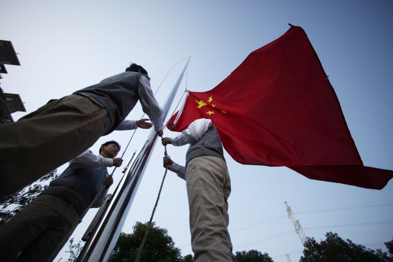 Young Pioneers raise the Chinese national flag during the weekly flag-raising ceremony at the East Experimental School in Shanghai on November 5, 2012. (REUTERS File Photo)