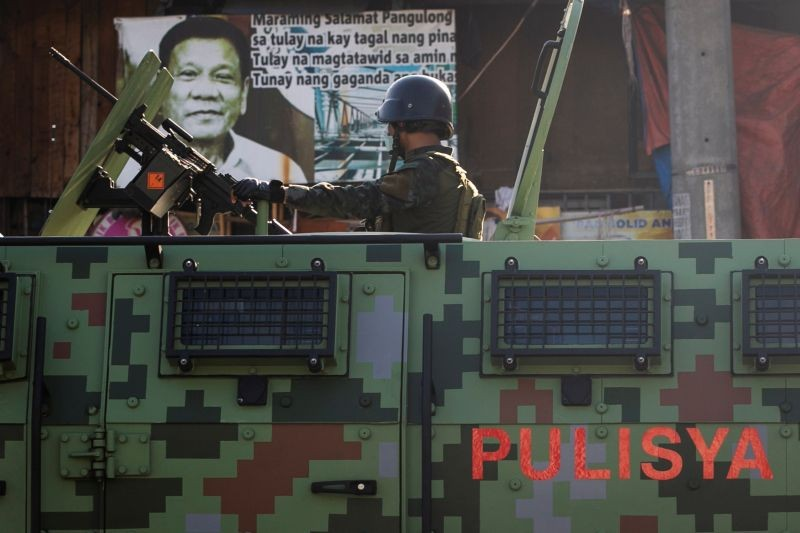 A police officer on board an armored vehicle drives past a poster of Philippines's President Rodrigo Duterte while patrolling a neighborhood to enforce the reimposed lockdown amid a spike in the coronavirus disease (COVID-19) cases, in Navotas, Metro Manila, Philippines on July 17, 2020. (REUTERS File Photo)