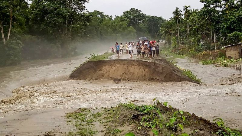 The district administrations have set up 224 relief camps and distribution centres in 16 districts, where 21,071 people have taken shelter, the ASDMA officials said. Above: People stand near an embankment after it was washed away by floodwater during heavy rainfall, at Pathsala in Barpeta district. (PTI Photo)