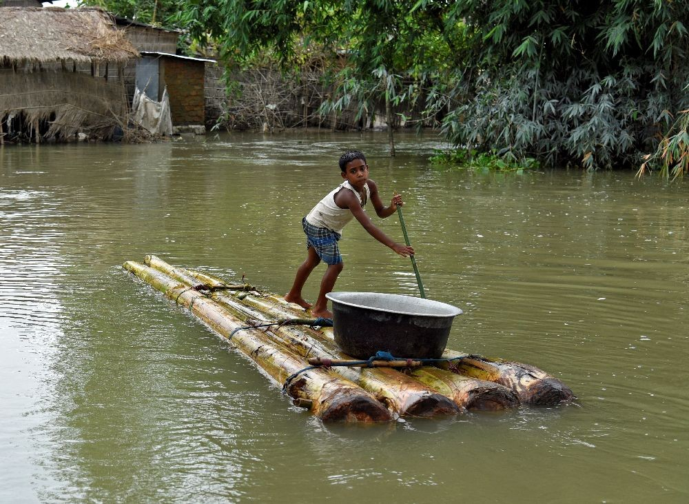 A boy transports a pot on a makeshift raft through a flooded area in Morigaon district, in the northeastern state of Assam, India, July 20, 2020. REUTERS/David Talukdar