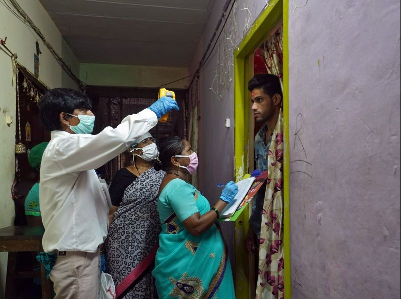 Health workers wearing protective face masks check the temperature of a resident at a housing society during a checkup campaign for the coronavirus disease (COVID-19) in Mumbai on July 21, 2020. (REUTERS Photo)
