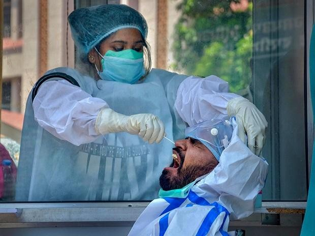 A medic collects samples from a man for COVID-19 swab tests at Civil Hospital, during the ongoing nationwide lockdown, in Amritsar. Photo: PTI
