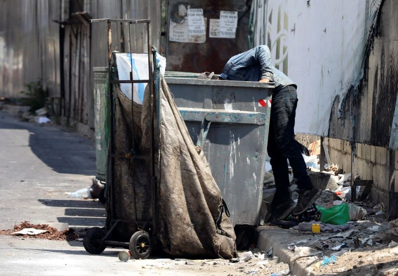 A man searches through a garbage bin in Beirut, Lebanon on June 30, 2020. (REUTERS File Photo)