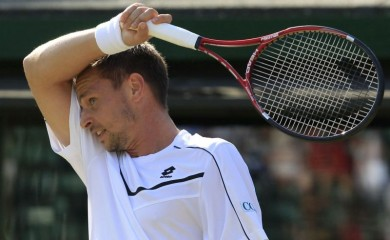 Robin Soderling of Sweden wipes his forehead during his match against Bernard Tomic of Australia at the Wimbledon tennis championships in London June 25, 2011. REUTERS/Suzanne Plunkett/File photo