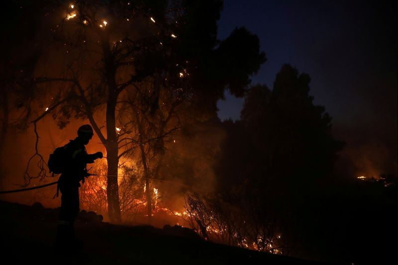 A firefighter sprays water to extinguish a wildfire burning near the village of Kechries, Greece on July 22, 2020. (REUTERS Photo)
