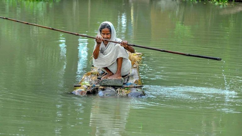 An elderly woman rows a makeshift raft to cross a flood-affected area of Mayoong village in Morigaon district of Assam. (PTI Photo)