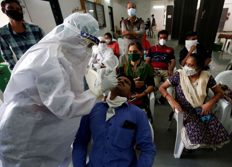 A healthcare worker wearing personal protective equipment (PPE) takes swab from a teacher of a municipal school for a rapid antigen test at a community center, amidst the coronavirus disease (COVID-19) outbreak, in Ahmedabad on July 27. (REUTERS Photo)
