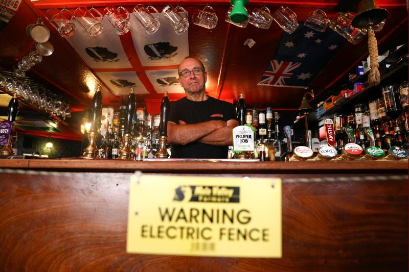 Landlord Johnny McFadden, 61, poses for a photo at the bar area of The Star Inn, where an electric fence has been installed at the bar area to ensure customers are socially distanced from staff while ordering drinks, following the outbreak of the coronavirus disease (COVID-19), in in St Just, Cornwall, Britain on July 14, 2020. (REUTERS Photo)