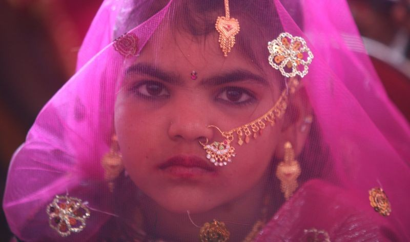 A veiled girl from the Saraniya community waits for her engagement ceremony to start at Vadia village in the western Indian state of Gujarat on March 11, 2012. (REUTERS File Photo)