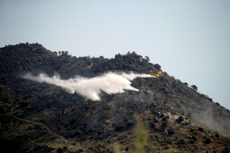 An airplane drops water as firefighters and Spanish Emergency Military Unit (UME) battle a wildfire in Robledo de Chavela, near Madrid, Spain on August 3. (REUTERS Photo)