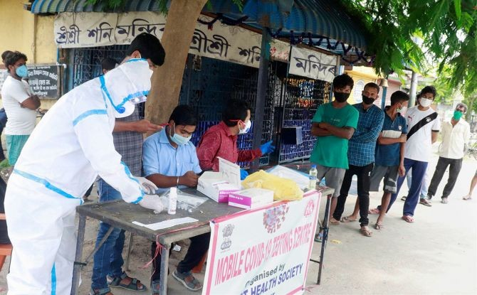 People stand in a queue to give their samples for COVID-19 test, in Tezpur, on Saturday. Photograph: PTI Photo