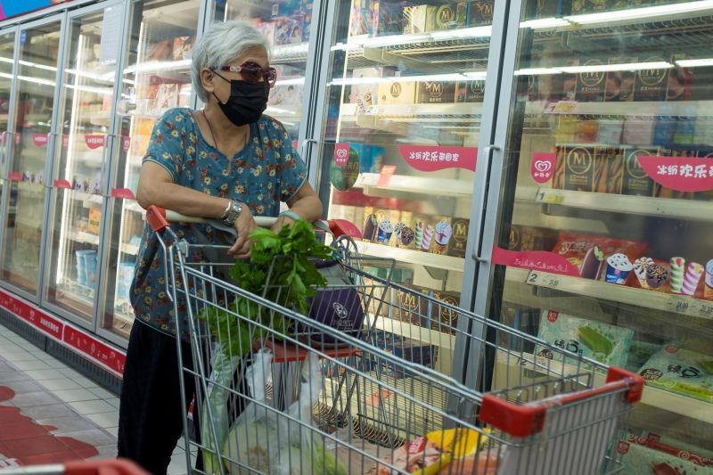 A woman looks at frozen food products in a supermarket following an outbreak of the coronavirus disease (COVID-19) in Beijing, China on  August 13, 2020. (REUTERS Photo)