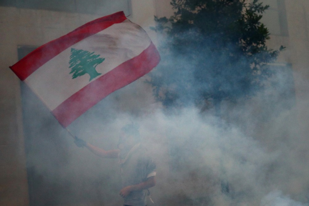 A demonstrator waves a Lebanese flag during anti-government protests that have been ignited by a massive explosion in Beirut on August 10, 2020. (REUTERS/Hannah McKay)