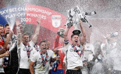Fulham's Tom Cairney lifts the trophy as he celebrates promotion to the premier league with teammates after winning the match, as play resumes behind closed doors following the outbreak of COVID-19. (Reuters Photo)