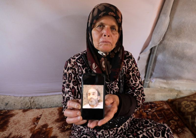 Fouziya al-Ghajar, 75, displays a picture of her deceased brother on a mobile phone, that she says was identified among thousands of images, smuggled out of Syria by a former Syrian military photographer code-named Caesar, that show bodies of dead detainees in Syrian government detention facilities, at an internally displaced persons camp tent in the opposition-held Idlib, Syria, July 11, 2020.  (REUTERS Photo)