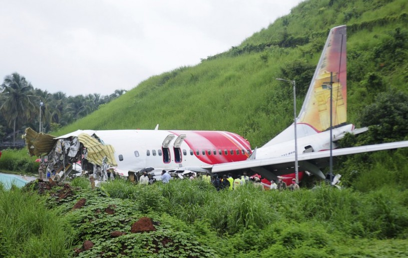 Officials stand on the debris of the Air India Express flight that skidded off a runway while landing in Kozhikode, Kerala state, India, Saturday, Aug. 8, 2020. The special evacuation flight bringing people home to India who had been trapped abroad because of the coronavirus skidded off the runway and split in two while landing in heavy rain killing more than a dozen people and injuring dozens more. (AP Photo/C.K.Thanseer)