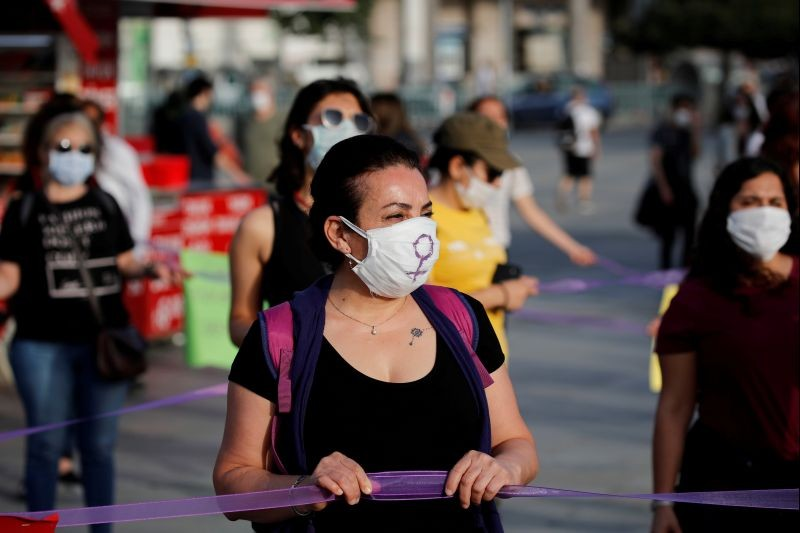Women wearing protective face masks keep social distance by holding onto purple ribbons as they protest for women rights and against child abuse, amid the spread of the coronavirus disease (COVID-19), in Istanbul, Turkey on May 20, 2020. (REUTERS File Photo)